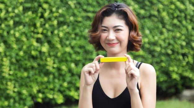 Focusdoos en hand van aziatische vrouw tonen product voor heden op openluchtpark