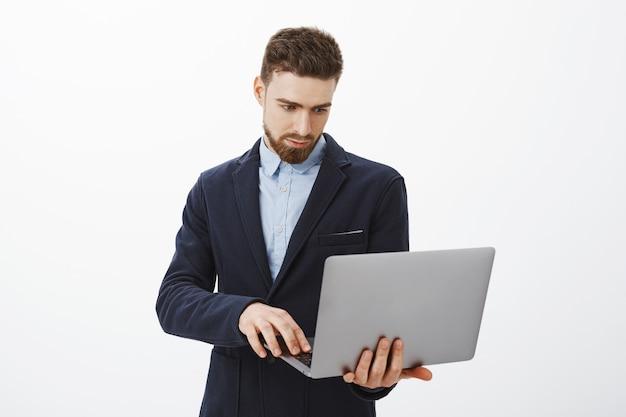Focussen op zaken. portret van slimme en ambitieuze geconcentreerde knappe jonge mannelijke ondernemer met baard en blauwe ogen laptop in de hand houden bladeren controleren schema met vastberaden blik