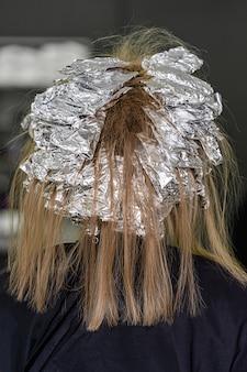 Folie op het haar van het model. trendy haarbleken met behulp van shatush-techniek. kijk van achteren