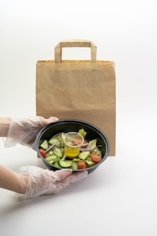 Folieplaten met voedsel in de hand van een vrouw, naast een papieren zak op een witte muur