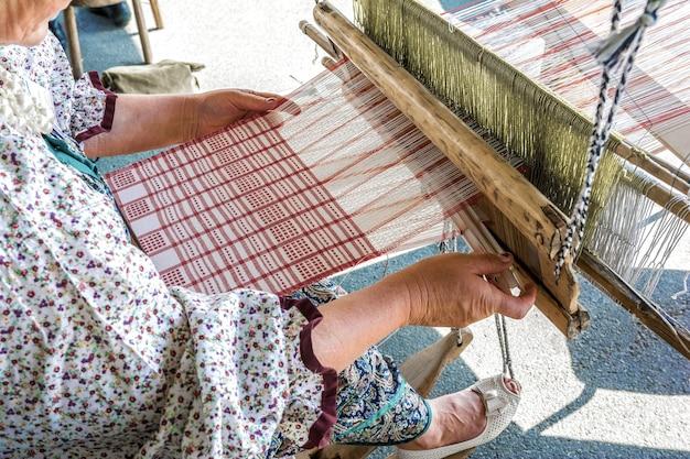 Folk art festival een vrouwelijke wever maakt stof op een handweefgetouw