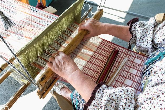 Folk art festival een vrouwelijke wever maakt stof op een ouderwets weefgetouw handgemaakte geweven producten