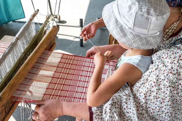 Folk art festival een wever leert een kind stof te maken op een handweefgetouw