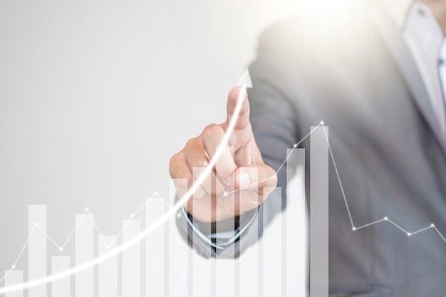 Fondsmanager hand schrijven toenemende grafiek naar schermmonitor