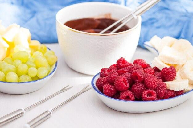 Fondue met gesmolten chocolade, fruit en bessen.