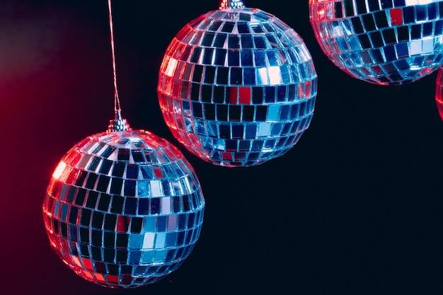 Fonkelende discoballen die in de lucht tegen zwarte achtergrond hangen
