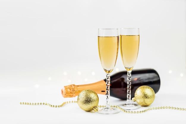 Fonkelende nieuwjaarachtergrond met champagne, fles en decoratie. kerstmis en gelukkig nieuw jaarconcept.
