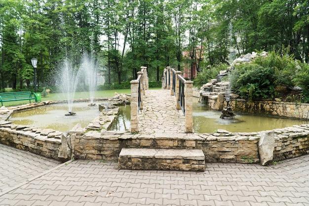 Fontein en brug van stenen tegels in het park. een decoratieve vijver buiten