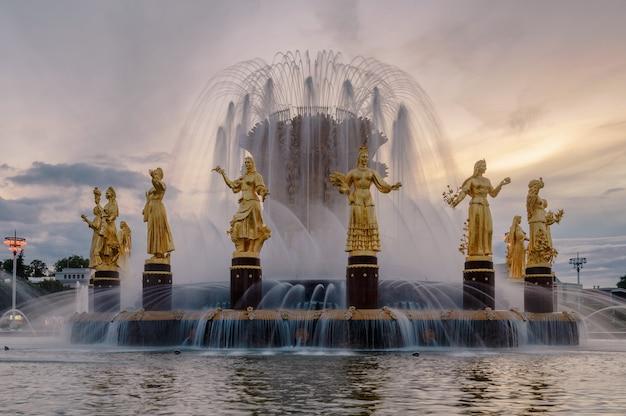 Fontein vriendschap van volkeren bij zonsondergang. een van de belangrijkste symbolen van het sovjettijdperk. zestien vrouwelijke beelden van de fontein vertegenwoordigen de 16 sovjetrepublieken. moskou. rusland.