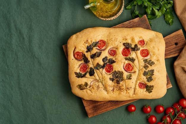 Food art focaccia flatbread met tomaten op donkergroen linnen textiel tafelkleed bovenaanzicht