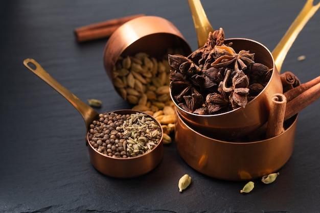 Food concept mix van masala kruiden, kaneel, venkel, steranijs, korianderzaad en kaneelpeulen in koperen beker op zwart leisteen bord