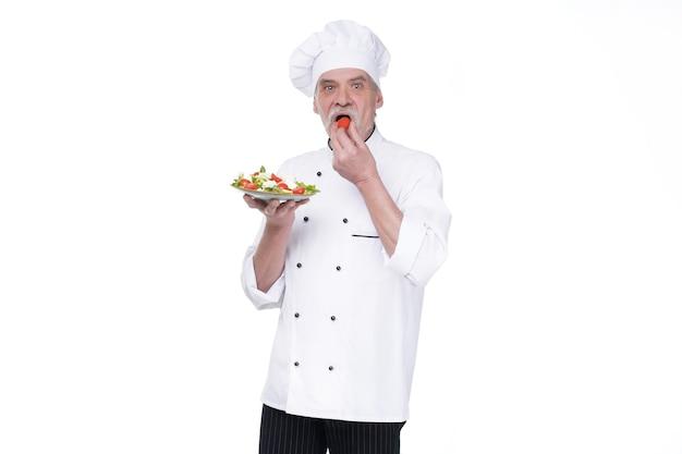 Foodservice, biologische voeding, gezonde voeding, koken en professioneel culinair concept, oudere chef-kok in wit uniform houdt groentesalade.