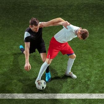 Football-speler die voor bal over groene grasmuur aanpakt. professionele mannelijke voetballers in beweging stadium. fit springende mannen in actie, springen, beweging in het spel.