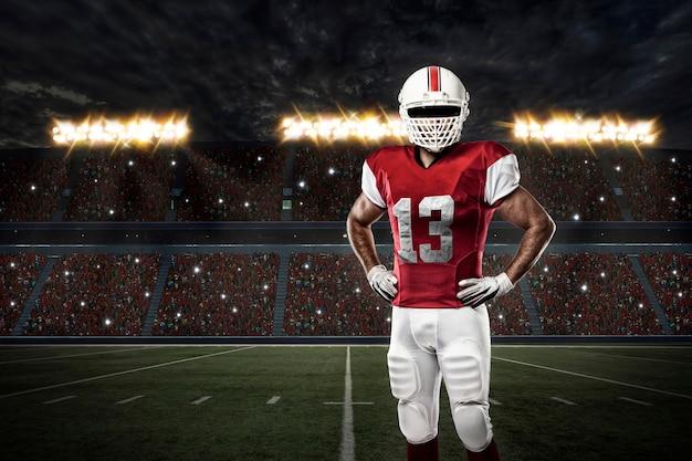 Football-speler met een rood uniform op een stadion.