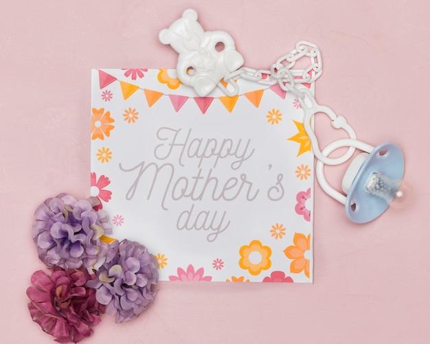 Fopspeen en bloemen met kaart voor moederdag