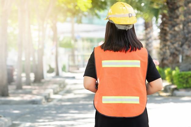 Foreman houdt toezicht op bouwwerkzaamheden en draagt reflecterende werkkleding voor de veiligheid op het werk.
