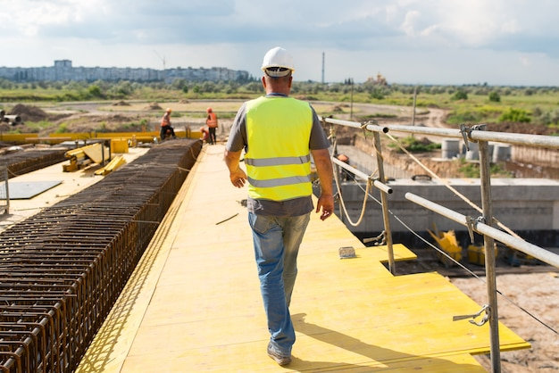 Foreman in een beschermende helm loopt langs de bouwplaats