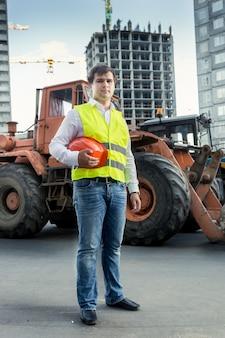 Foreman in gele veiligheidsvest poseren naast bulldozer op bouwplaats