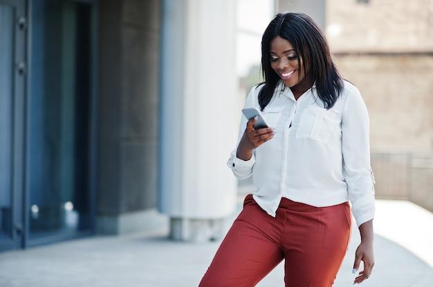 Formeel geklede afro-amerikaanse zakenvrouw in witte blouse en rode broek met mobiele telefoon. succesvolle donkere huid zakenvrouw.