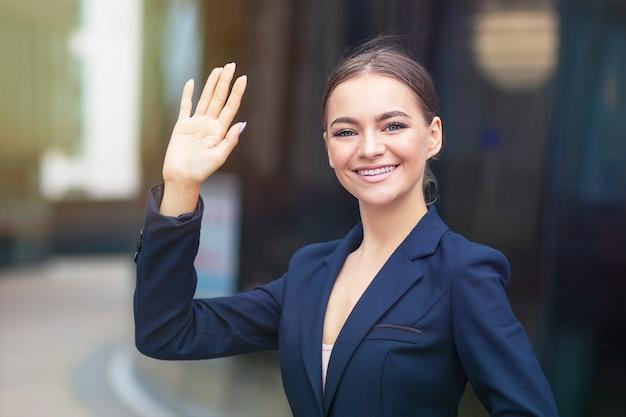 Formeel geklede gelukkige zakenvrouw zwaait met haar hand buitenshuis