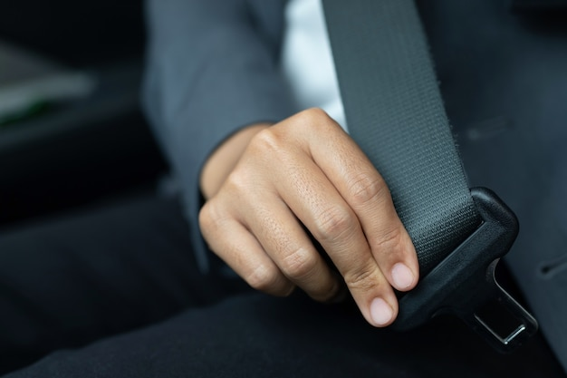 Formeel geklede vrouw die veiligheidsgordel draagt tijdens het rijden
