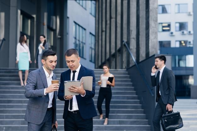 Formeel geklede zakenlieden die buiten het kantoorgebouw spreken en lopen. zakenman iets bespreken en betwisten met blanke zakenman met tabletcomputer in handen.
