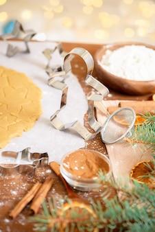 Formulieren voor peperkoek kerstmannen en sterren, close-up, bovenaanzicht, rauw deeg met kaneel, bereid om te bakken.