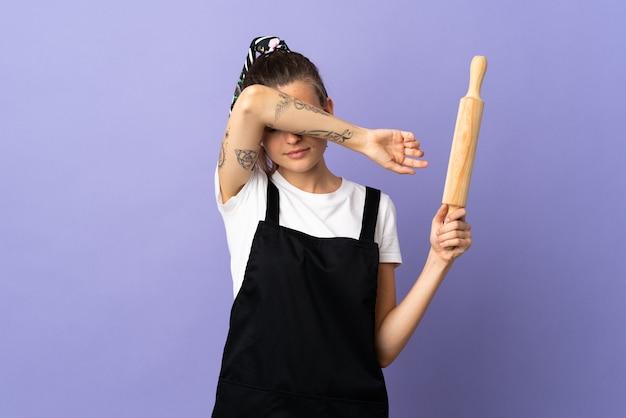 Fornuis slowaakse vrouw geïsoleerd op paarse muur die ogen behandelt door handen