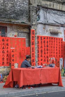 Foshan, provincie guangdong, china. 8 februari 2021. een kalligraaf schrijft spring festival couplets voor mensen. het is de meest voorkomende en belangrijkste gewoonte bij het vieren van chinees nieuwjaar.