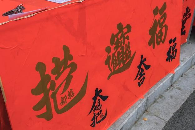 Foshan, provincie guangdong, china. 8 februari 2021. mensen die coupletten schrijven met groeten voor het lentefestival. voorbereiding voor chinese nieuwjaarsviering in de kuaizi-straat in foshan