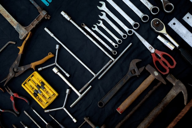 Foto bovenaanzicht een enorme verzameling van werkende hand- en elektrisch gereedschap veel voor de houten op geïsoleerde zwarte ondergrond