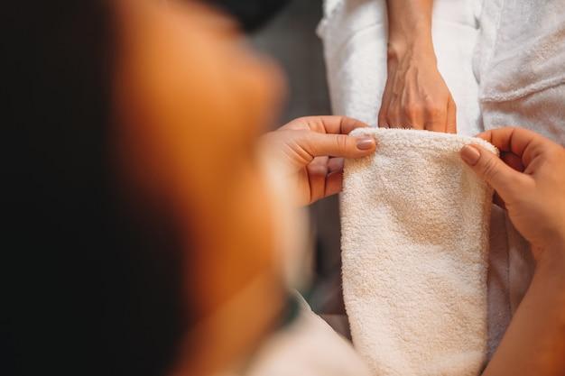 Foto bovenaanzicht van blanke werknemer die de massageprocedure afmaakt door een speciale warme handschoen toe te passen