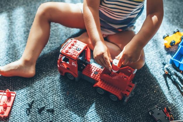 Foto bovenaanzicht van een blanke jongen die met een constructeursauto op de vloer speelt