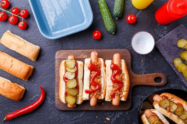Foto bovenop broodjes met worst op snijplank, op tafel met komkommers