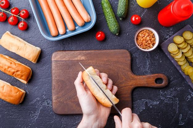 Foto bovenop de tafel met ingrediënten voor hotdogs, snijplank, man's handen