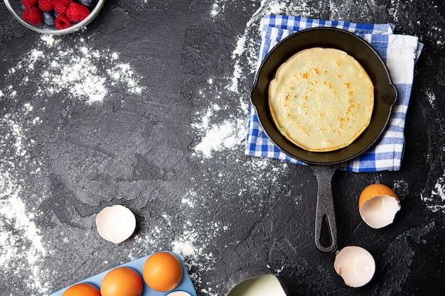 Foto bovenop eieren, melk, bessen, pan met pannenkoeken, handdoeken op zwarte tafel. ingrediënten voor pannenkoeken