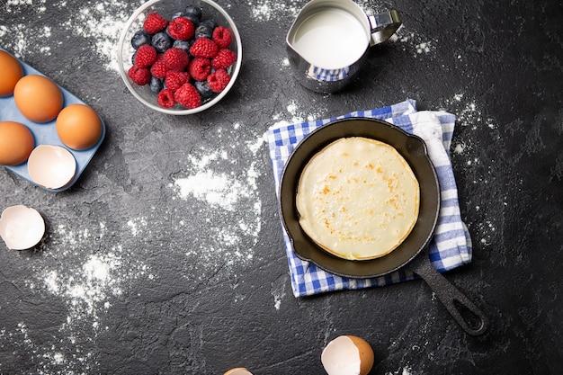 Foto bovenop eieren, melk, bloem, bessen op zwarte lijst. ingrediënten voor pannenkoeken