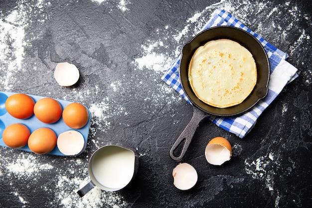 Foto bovenop eieren, melk, pan met pannenkoeken, handdoeken op zwarte lijst. ingrediënten voor pannenkoeken