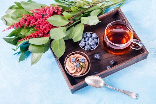 Foto bovenop rode bloemen, cake, bessen, zwarte thee op houten dienblad