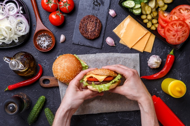 Foto bovenop twee hamburgers, menselijke handen, chilipepers,