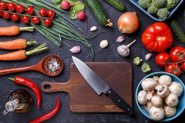 Foto bovenop verse groenten, champignons, snijplank, olie, mes