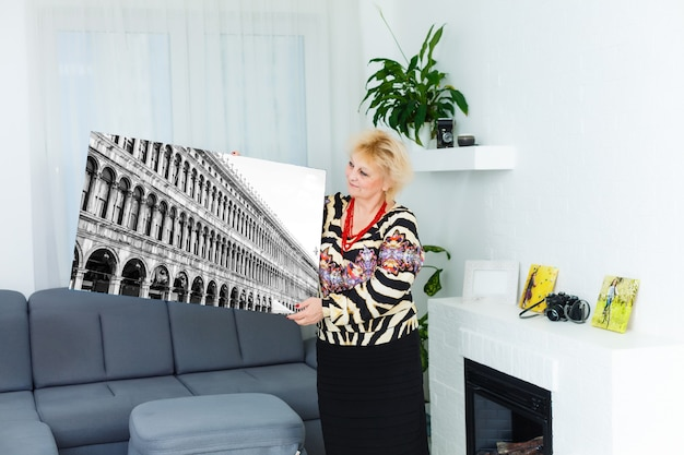 Foto canvas. blonde oudere vrouw die zich gemotiveerd voelt tijdens het maken van fotocanvas