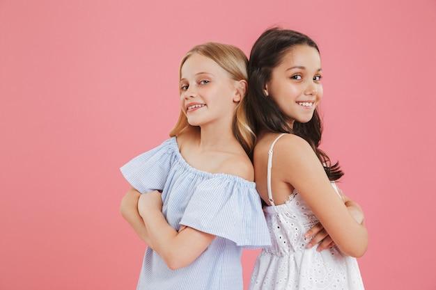 Foto close-up van brunette en blonde vriendinnen die jurken dragen die glimlachen en kijken terwijl ze rug aan rug staan met gekruiste armen.