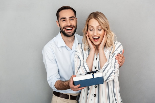 Foto close-up van een gelukkige man in casual kleding die lacht en cadeau geeft aan zijn vriendin geïsoleerd over grijze muur