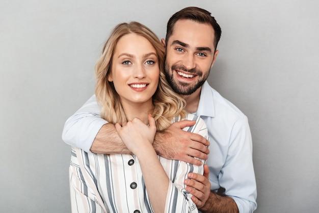 Foto close-up van een vrolijk paar in casual kleding glimlachend en knuffelen elkaar geïsoleerd