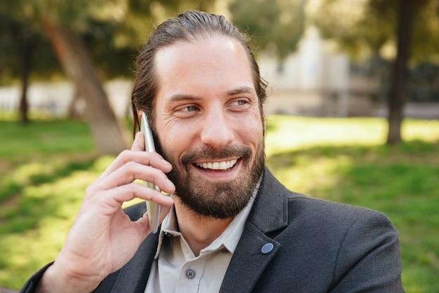 Foto close-up van gelukkig bebaarde man 30s in formele pak glimlachend en praten over smartphone, zittend op een bankje in stadspark tijdens zonnige dag