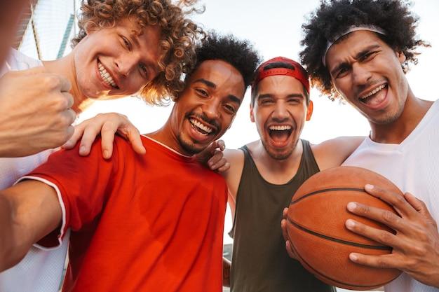 Foto close-up van knappe spelers mannen glimlachen en selfie nemen, tijdens het spelen van basketbal op speelplaats buiten tijdens zonnige zomerdag