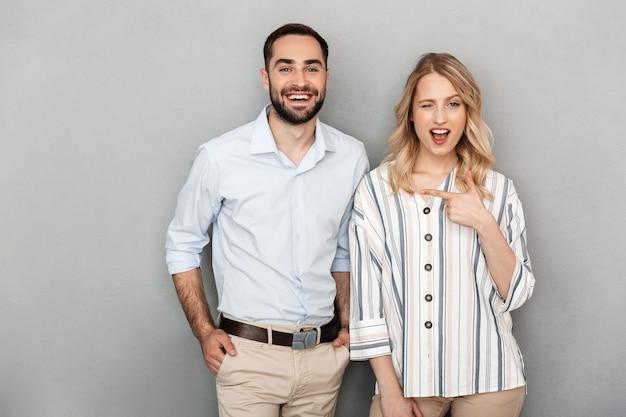 Foto close-up van lachend paar in casual kleding glimlachend terwijl vrouw wijzende vinger naar man geïsoleerd