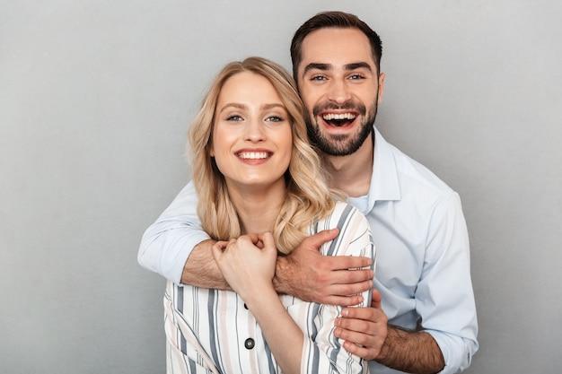 Foto close-up van schattig paar in casual kleding glimlachend en knuffelen elkaar geïsoleerd over grijze muur