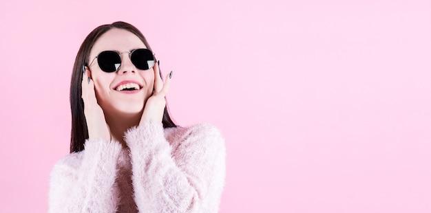 Foto close-up van seksuele charmante vrouw 20s met lang kapsel trendy zonnebril dragen camera kijken met fashion look geïsoleerd op roze achtergrond